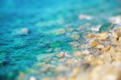 Rocky coast with clean blue see-through water. Miniature Stock Photo