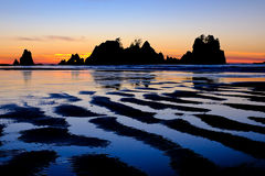 Rocky Coast and Colorful Sunset Reflected in the Tide. Royalty Free Stock Photo
