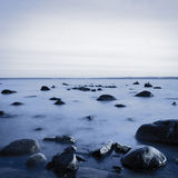 Rocky coast in the evening. Long exposure shot Stock Photos