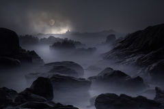 Rocky coast in a full moon night. Rocky sea coast in an overcast full moon night Royalty Free Stock Images
