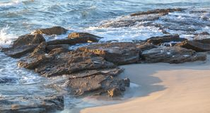 Rocky coast and lapping ocean. Rocks buried deep in sand holding back the erosion from consistent and persistent erosion from a relentless sea. Demonstrating royalty free stock images