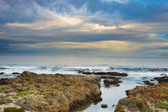 Rocky coast line on the ocean at De Kelders, South Africa, famous for whale watching. Winter season, cloudy and dramatic sky. Stock Images