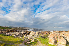 Rocky coast line on the ocean at De Kelders, South Africa, famous for whale watching. Winter season, cloudy and dramatic sky. Rocky coast line on the ocean at Royalty Free Stock Photos
