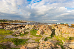 Rocky coast line on the ocean at De Kelders, South Africa, famous for whale watching. Winter season, cloudy and dramatic sky. Rocky coast line on the ocean at Stock Images