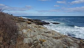 Rocky Coast mammoth rocks ocean geologic with sky. Striated geologic glacial formation along the Atlantic Ocean Coast in Maine in April, surf beating on black Royalty Free Stock Photography