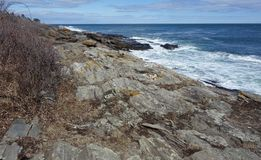 Rocky Coast mammoth rocks ocean geologic. Striated geologic glacial formation along the Atlantic Ocean Coast in Maine in April, surf beating on black rocks, deep Royalty Free Stock Photos