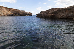 Rocky coast of  Mediterranean Sea with blue water on Malta Stock Images