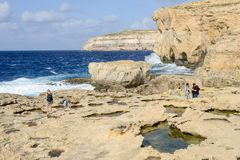 The rocky coast near missing Azure Window in Gozo Island, Malta. Gozo island, Malta - 30 October 2017: people walking on the rocky coast near missing Azure Royalty Free Stock Images