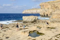 The rocky coast near missing Azure Window in Gozo Island, Malta. Gozo island, Malta - 30 October 2017: people walking on the rocky coast near missing Azure Royalty Free Stock Photography