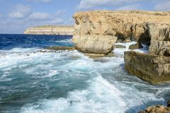 The rocky coast near missing Azure Window in Gozo Island, Malta. Wave splashing on the rocky coast near missing Azure Window in Gozo Island, Malta Royalty Free Stock Photos