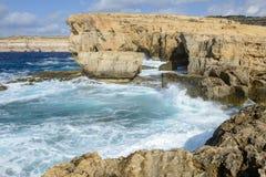The rocky coast near missing Azure Window in Gozo Island, Malta. Wave splashing on the rocky coast near missing Azure Window in Gozo Island, Malta Royalty Free Stock Images