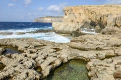 The rocky coast near missing Azure Window in Gozo Island, Malta. Wave splashing on the rocky coast near missing Azure Window in Gozo Island, Malta Royalty Free Stock Image
