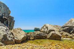 The rocky coast  overlooking the turquoise blue sea in warm summ Royalty Free Stock Photography