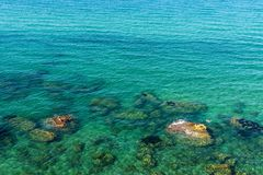 Rocky coast in summer in Sicily, Italy. Rocky coast with people bathing and diving in summer in Castellammare del Golfo in Sicily, Italy Royalty Free Stock Photo