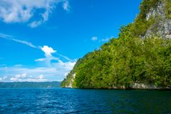 Rocky Coast with a Rainforest and a Sailing Yacht. Indonesia. Rocky coast of a tropical island in sunny weather. Rainforest on a slope. Sailing ship in the Royalty Free Stock Photos