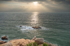 Rocky coast, sea and sunbeams in the sky Royalty Free Stock Photos