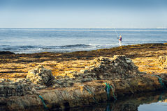 Rocky Coast and See with Fisherman Stock Image