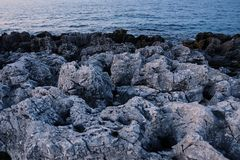 Rocky coast. Sharp stone rows, breaking waves. Majestic landscapes blue tint stock photography