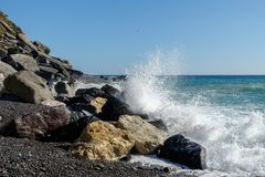 Rocky coast with splashing wave. In Cinque Terre, Italy Stock Photos
