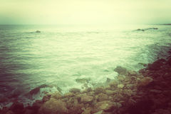 Rocky coast and stormy sea in green glow Stock Photography