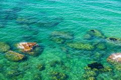 Rocky coast in summer in Sicily, Italy. Rocky coast with people bathing in summer in Castellammare del Golfo in Sicily, Italy Royalty Free Stock Photography