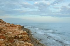 Rocky coast on sunset on a cloudy evening Royalty Free Stock Photography