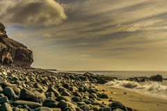 Rocky coast at sunset with dark clouds Royalty Free Stock Photo