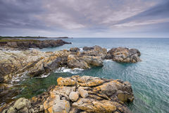 Rocky coast under cloudy skies Stock Images