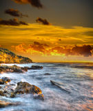 Rocky coast under a scenic sky at sunset Stock Photos