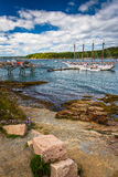 Rocky coast and view of boats in the harbor at Bar Harbor, Maine Stock Photography