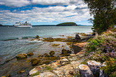 Rocky coast and view of cruise ship and island in Frenchman Bay Royalty Free Stock Photos