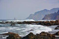 Rocky coast,waves  and mountains Stock Photos