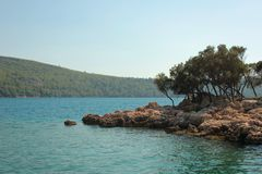 Blue lagoon in the Aegean Sea. Rocky coast, on which there is a beautiful pine forest. Hot summer sunny day. The right place and time for vacation royalty free stock image