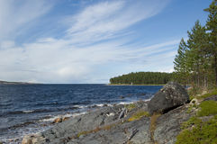 The rocky coast of the White sea. The rocky islands covered with coniferous wood in the White sea. Quiet water, the blue sky, white clouds, white sail stock photo