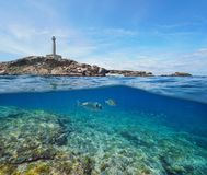 Free Rocky Coast With A Lighthouse And Fish Underwater, Split View Half Above And Below Water Surface Royalty Free Stock Images - 131683479