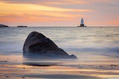 Rocky Coastal Lighthouse Seascape en la puesta del sol foto de archivo libre de regalías