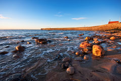 Rocky coastal scene in warm sunrise light. A rocky coastal scene in warm sunrise lighting. Pier and blue sky in the background. Photo taken in Anstruther Royalty Free Stock Photos