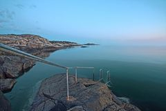Rocky coastline. Scenic view of rocky coastline with metal hand rail in foreground stock photography