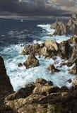 Rocky Coastline. A storm tossed sea along a rocky coastline with sailboat Stock Image