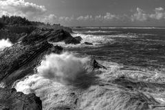 Rocky Coastline. Waves and rough sea cresting and crashing against shoreline in Black and White Royalty Free Stock Photo