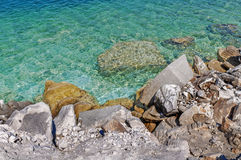 Rocky coastline beach with an old stone wall, bushes and trees o Royalty Free Stock Photos
