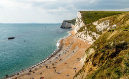 Rocky Coastline and Beach. The rocky coastline and pebble beach being enjoyed by people on a warm sunny day in summer. Located at Durdle Door, part of the Stock Photo