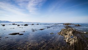 Rocky coastline with blue skies Stock Image