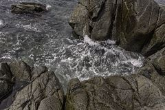 Rocky coastline and dark green sea water. With white foam Stock Photography