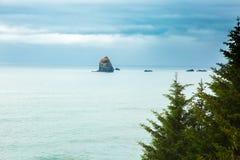 Rocky Coastline de Oregon en las rocas monolíticas del pajar de la distancia imágenes de archivo libres de regalías