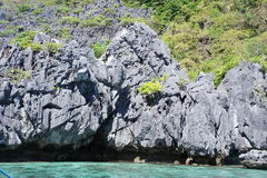 Rocky coastline on a deserted island near El Nido, Palawan, Philippines. Cliff breaking in ocean waves one uninhabited island near El Nido, Palawan, Philippines Royalty Free Stock Photo