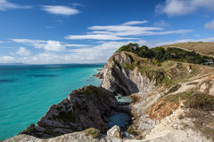 Rocky coastline in Dorset, England on summer day with blue sky. Stunning coastal scene in Dorset, England Royalty Free Stock Photography