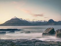 Rocky coastline in Elgol at sunset with cracked rocks in detail, Isle of Skye, Scotland. Blue shadows Stock Images