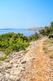 Rocky coastline with a foot path and bushes and trees by the Adr Royalty Free Stock Images