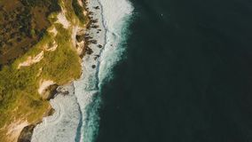 Rocky coastline on the island of Bali. Aerial view. Aerial view of rocky coast with surf the waves off the at sunset, Bali,Indonesia, Pura Uluwatu cliff. Waves stock video